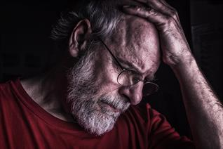 an older man holding his head in pain
