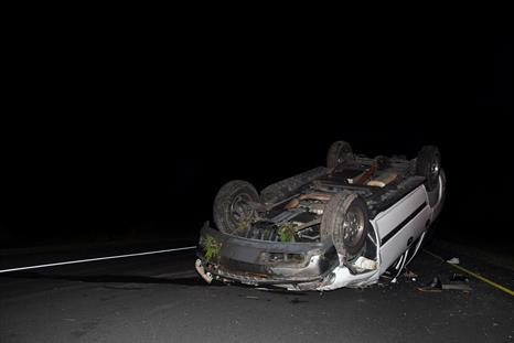 an overturned car on a road at night